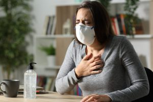 caucasian woman with brown hair and a mask on grabbing her chest