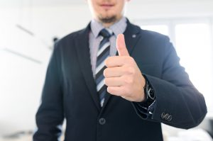 caucasian man in a suit with his thumb up
