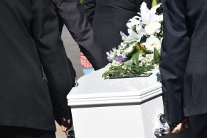 white casket being carried by men in black suits.