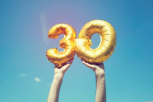 two gold balloons being held up by caucasian hands making the number thirty