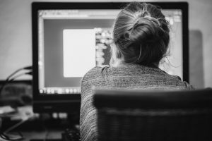 black and white photo of the back of a woman sitting in front of a computer screen.