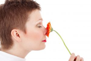 caucasian woman smelling an orange flower on her nose.