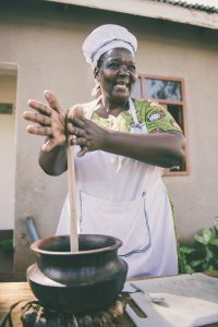 african american woman with a white apron on with her hands on a long stick that is in a pot