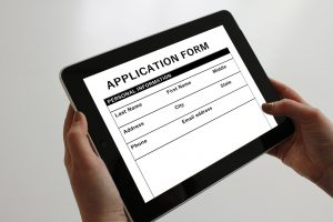 application form on a tablet with hands holding the tablet.