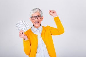 older Caucasian woman with a yellow cardigan on holding money in her hand with the other hand pumped up