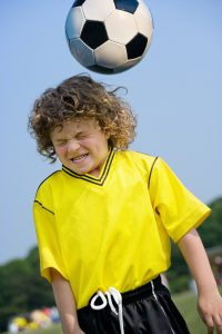 young boy in a yellow shirt and shorts with a soccer coming towards his head.