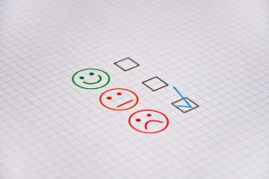 a green smile face, orange straight face and red sad face with a checkmark in the box next to the red one.