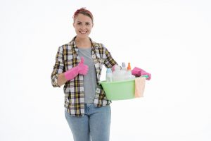 caucasian woman holding a bucket with cleaning supplies in it