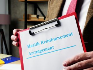 health reimbursement arrangement written in blue on a paper that is on a clipboard being held by hands