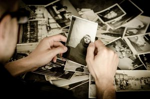 older caucasian hands holding up an old photo with other laying around.