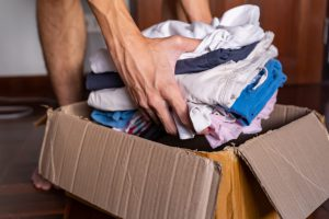 caucasian hands putting a pile of clothes into a brown box.