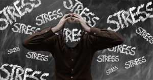 man with his hands on his head with the word stress on his face and stress written on a blackboard behind him.