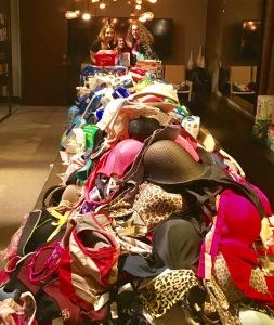 hundreds of different colored bras on a long table.