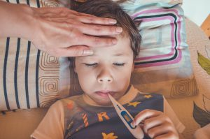 young boy in bed with a thermometer in his mouth and an adults hand on his forehead.