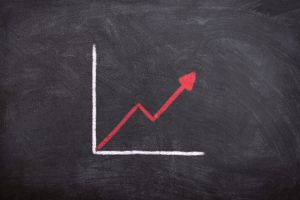 graph on a chalkboard with a red arrow going upward