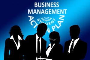 silhouettes of 4 people in business suits with business management as the headline