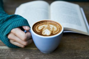 a caucasian hand holding a coffee mug with coffee in it and an open book behind the cup.