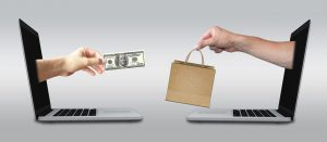 one hand coming out of a laptop with a hundred dollar bill giving it to another hand coming out of a laptop with a shopping bag.
