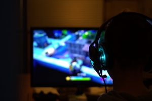 silhouette of a person with a headset on with video games on the screen.