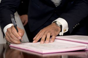 mans hands in a suit signing paperwork
