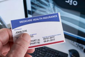 medicare card with the name john doe on it and an x-ray in the background