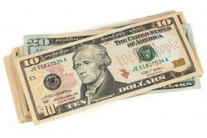 ten dollar bill on top of a twenty dollar bill and more bills.