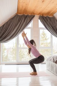woman standing in a yoga position in her room