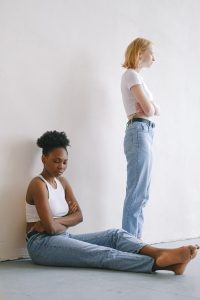 caucasian woman standing with her back to the young african american woman sitting on the floor looking away from her with her hands crossed.