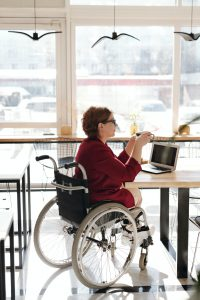 caucasian woman sitting in a wheelchair at a table