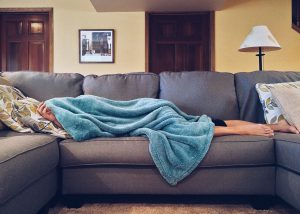 caucasian person laying on a couch with a blue blanket over them