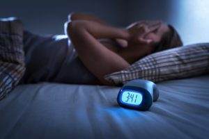 woman laying in bed on her back with her hands on her eyes and a clock on the bed that says 3:41