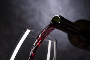 red wine being poured into a glass from the bottle