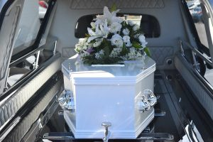 white casket with white flowers on top of it in a car