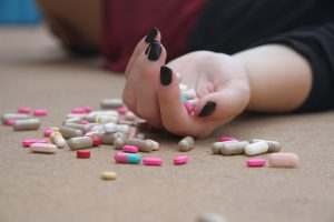 caucasian hand laying on the floor with pills in it and on the floor