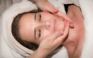 caucasian woman laying down with a towel on her head getting her faced massaged