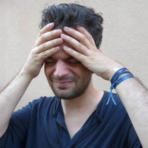 caucasian man holding his forehead with his hands