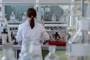 woman in a lab coat working on vials.