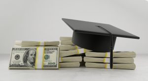 graduation cap on top of stacks of hundred dollar bills