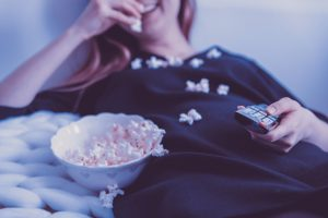 caucasian woman sitting down with a remote in one hand and the other with popcorn from a bowl next to her.