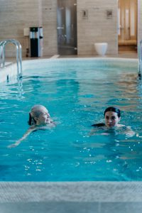 older woman and younger woman swimming in a pool