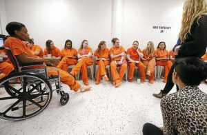 women in orange jumpsuits sitting in an open circle