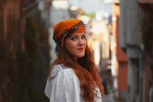 caucasian woman with red hair smilingwith an orange scarf on her head.