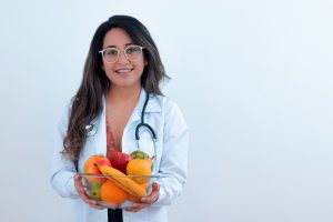 young woman with a stethoscope around her neck holding a bowl of fruit.