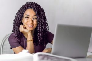 young african american woman smiling with a laptop in front of her.