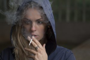 caucasian woman with her hood up smoking a cigarette