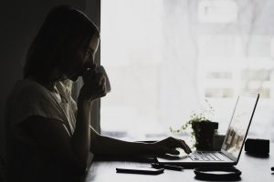 woman sitting at a desk with coffee in her hand and looking at a laptop