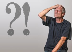 a caucasian man with his hand on his head with a question mark and exclamation mark next to him