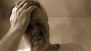 older caucasian man with his hand to his head