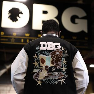 letterman jacket with the letters DBG on it and a picture of a person with scrapes on their face and hands holding a book