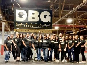 a group of people standing next to each other smiling with a DBG banner above them.